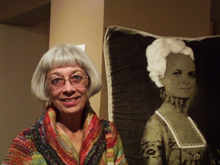 Catherine Sullivan, the curator for the Janet Turner Print Museum, stands next to a printed pillow submitted to the Janet Turner National Print Competition.Photo credit: Frances Mansour