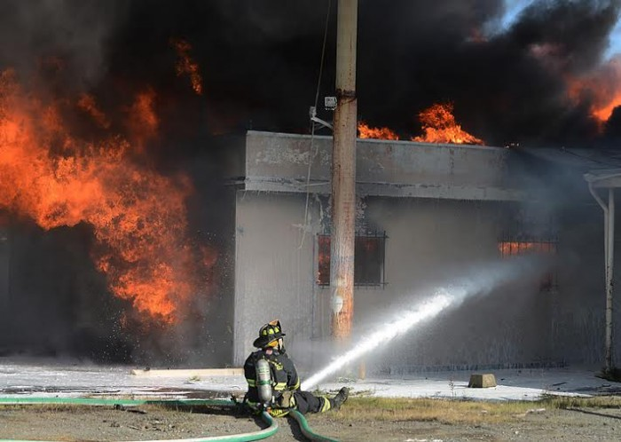 Campbell attends to a fire with a high-pressure hose. Photo Courtesy of Jesse Campbell.