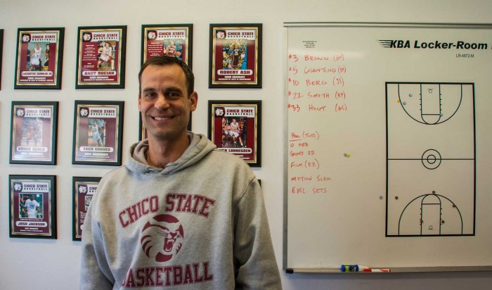 Chico State men's basketball coach Greg Clink poses in front of his former players plaques. Photo credit: Alex Boesch