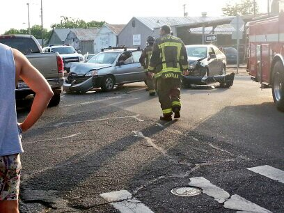 Firefighters approach the aftermath of a four-car pileup on the intersection of Ninth and Ivy streets. Photo credit: Emerson Keenan