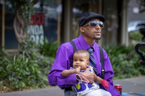 Jamari Caldwell sits with his daughter at the Thursday Night Market during the spread of Paint the Town Purple. He is supporting Relay for Life by wearing purple to raise awareness for the fight against cancer. Photo credit: Maisee Lee