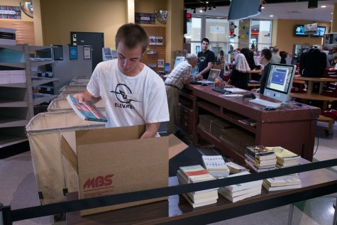 Business Marketing major and bookstore employee Kyle Sacher sorting books at the Wildcat Store. Photo credit: Matthew Vacca