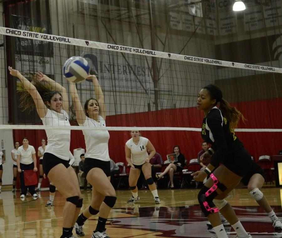 Freshman middle hitter Natalie Nordahl, left, and junior middle hitter Kristyn Casalino block a shot by the Lumberjacks last season. Chico State beat Cal State East Bay on Friday. Orion File Photo.