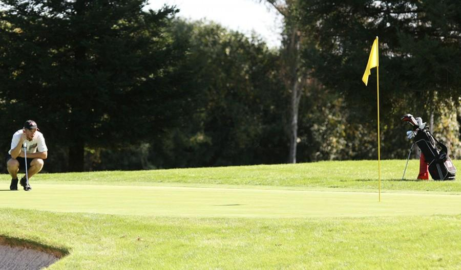 Chico State golfer Lee Gearhart examines the green before making a putt. Photo credit: John Domogma