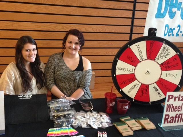Diana Hass (left) and Athena Oreck, both senior recreation, hospitality and parks management majors, man the prize wheel on the last day of De-Stress Fest. Photo credit: Amanda Rhine
