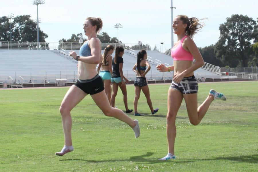 Kody Atkins and Nicole Anthony run during practice on Wednesday before hitting the weight room. Photo by John Domogma.