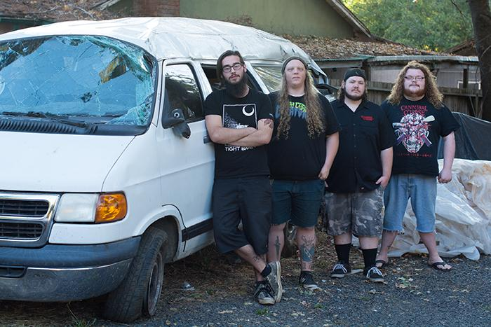 Members of the band, Aberrance, (from left) Ed Vance, Jake Hollingsworth, David Hordienko, and Nick Rahming hang out with their retired tour van on Tuesday. Photo credit: Alicia Brogden
