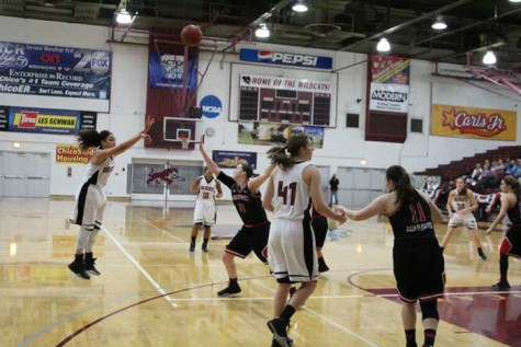 Sophomore Whitney Branham launches a three point shot as her team looks on against Simpson University on Jan 23. Photo credit: Jordan Olesen