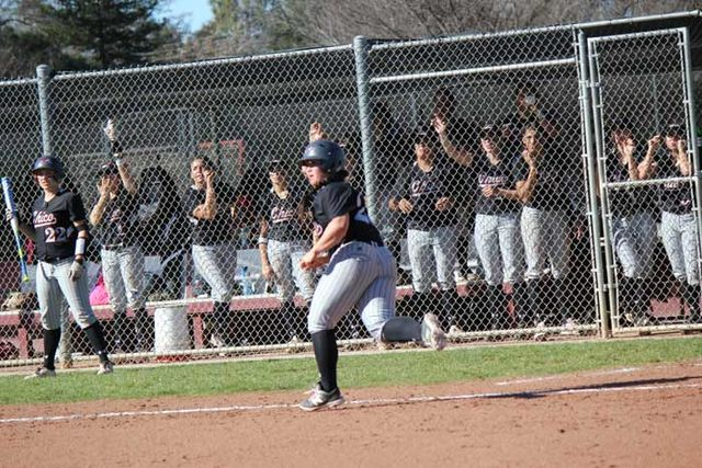 Junior Cyrena Taylor runs to first base as her team cheers her on during the game against Dominican University on Feb. 7.