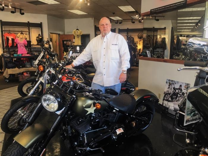 Stephan Adams poses with new bikes in his Harley Davidson store Photo credit: Elizabeth Helmer