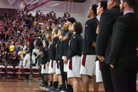 The men's basketball team lines up during the National Anthem in a game against Cal Poly Pomona.