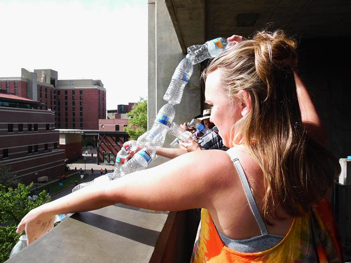 Molly Marcussen lowering the bottles that will eventually hang from the third floor of Butte Hall. Photo credit: George Johnston