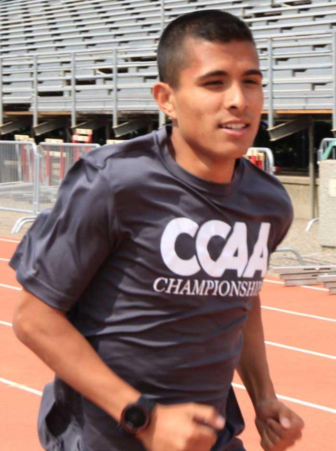 Junior+runner+Steven+Martinez+runs+around+the+track+during+practice.+Photo+credit%3A+Cam+Lesslie