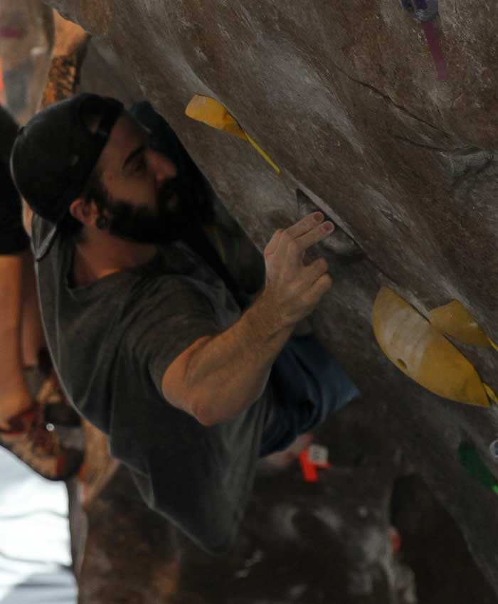 Climber Justin Caswell climbs along side his fellow competitors.