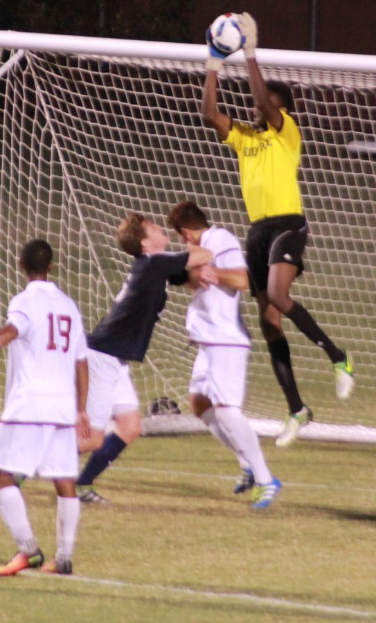 Goalkeeper Damion Lewis makes a save during a Wildcat's home game while a fight occurs on the field. Photo credit: Royal T Lee-Castine