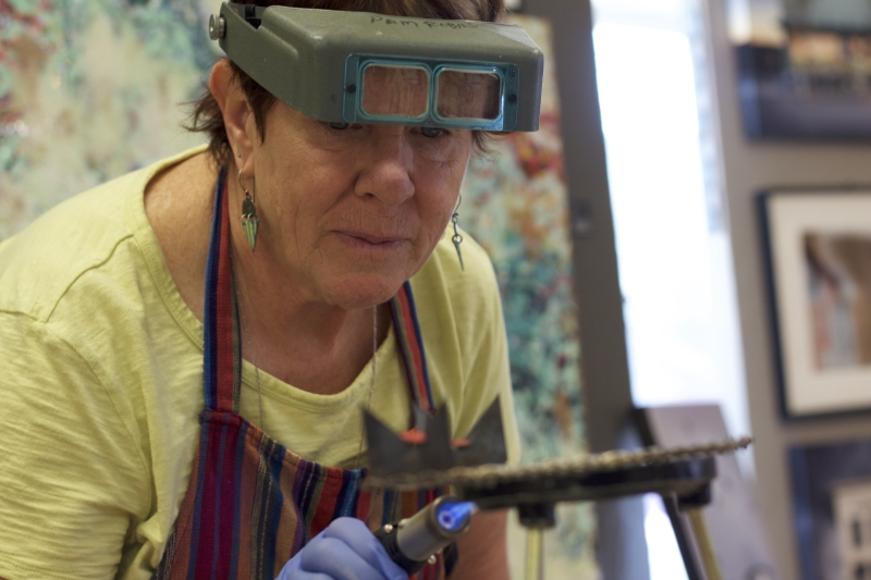 Pamela+Robinson+shows+how+to+burn+color+onto+jewelry.+Photo+credit%3A+Caitlyn+Young