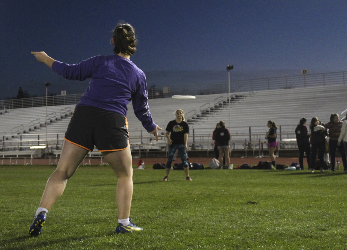 Annabelle Cole, a freshman on Chico's Women's Ultimate team flicking a disc to teammate Rose McDonough before a late-night practice at the University Stadium. Photo credit: Anne Chamberlain