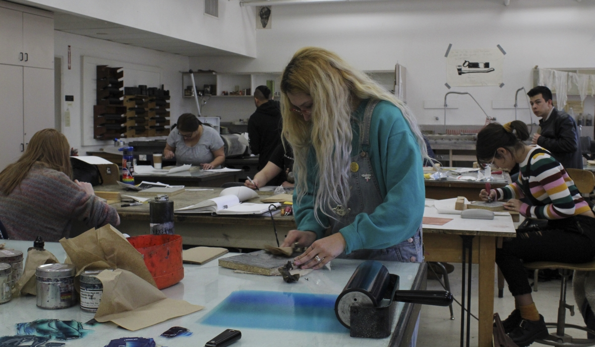 Intro to Printmaking students Sonya Gaysinskiy, Jillian Harris-Rivera, and Valerie Hill hard at work on their linoleum block relief prints at Ayres Hall Monday morning. Photo credit: Anne Chamberlain