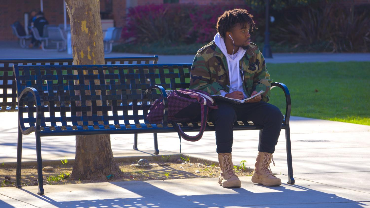 Nathaniel Nevels writes rhymes as he enjoys the sunshine at Chico State on Thursday. Photo credit: Carly Maxstone