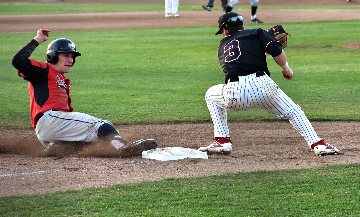 Cameron Santos, right, tries to tag out Kyle Redford, left, at third base in the top of the first in the second February 9 game against Northwest Nazarene.