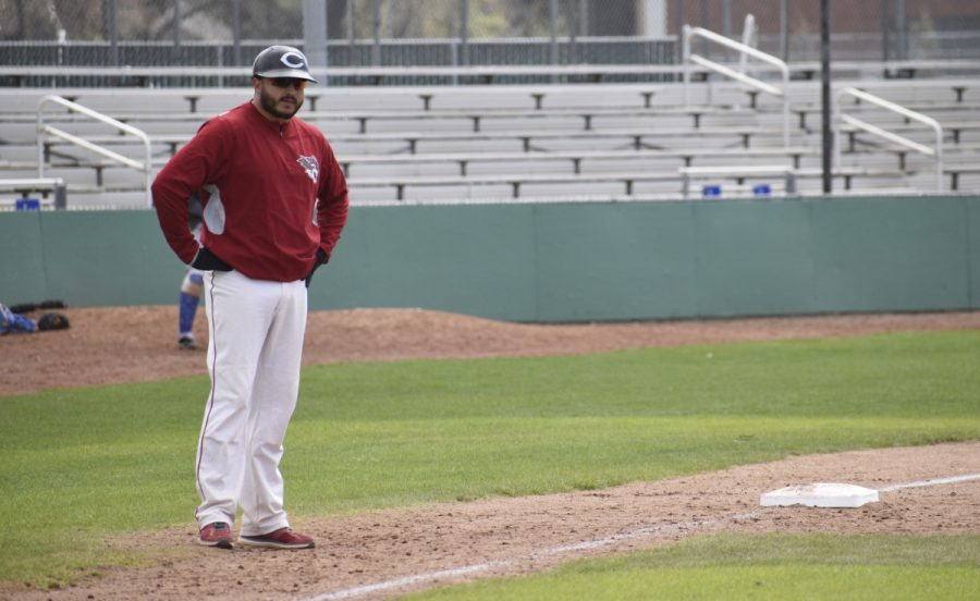 Third base coach Jose Garcia looks at one of his players on first base to give him a sign. Photo Credit: Alex Grant