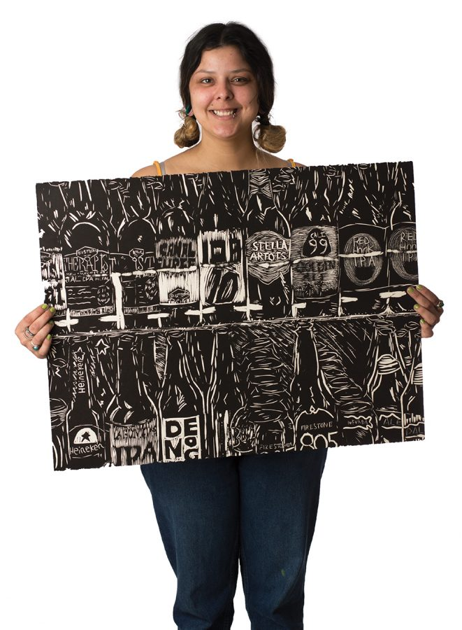 Marisa+Sergovia+holds+up+one+of+her+paintings.+Photo+credit%3A+Sean+Martens