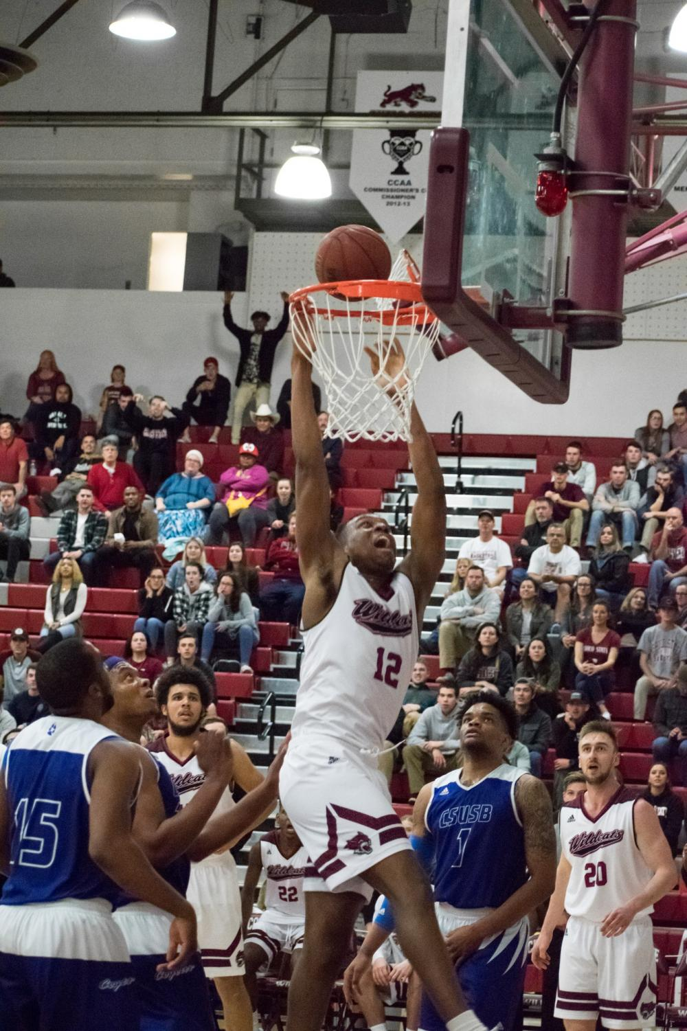 Junior forward, Marvin Timothy throws down a dunk for the Wildcats. Photo credit: Kate Angeles