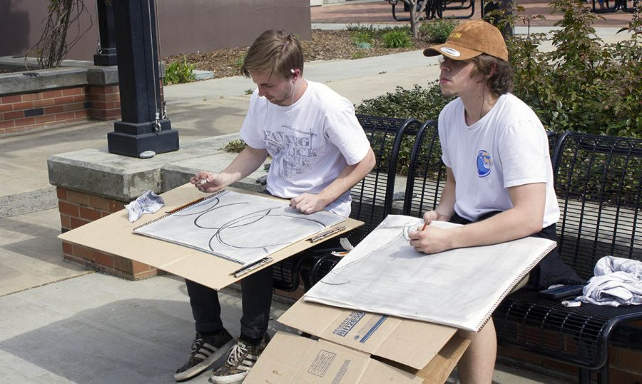 Eli Grusin, left, and Tyler Munstock, right, draw the Ring Roll sculpture on campus as part of an art class on March 29. Photo credit: Martin Chang