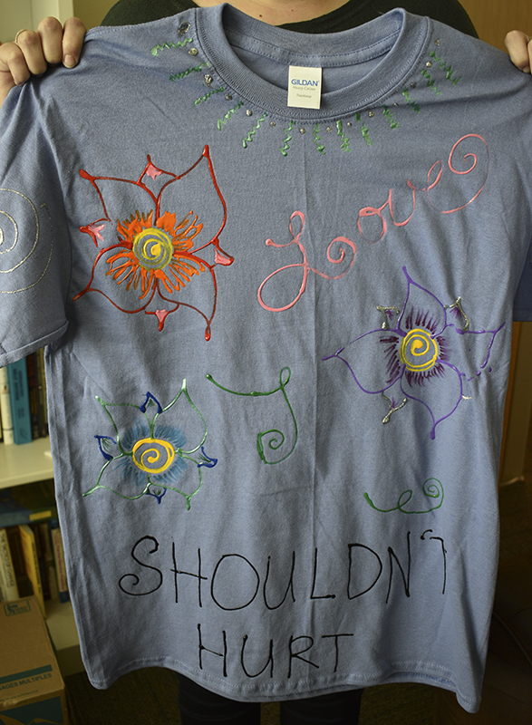 Alix MacDonald holds up an example of a Clothesline Project shirt. All students are welcome to design a shirt any way they want to express their feelings on sexual assault.