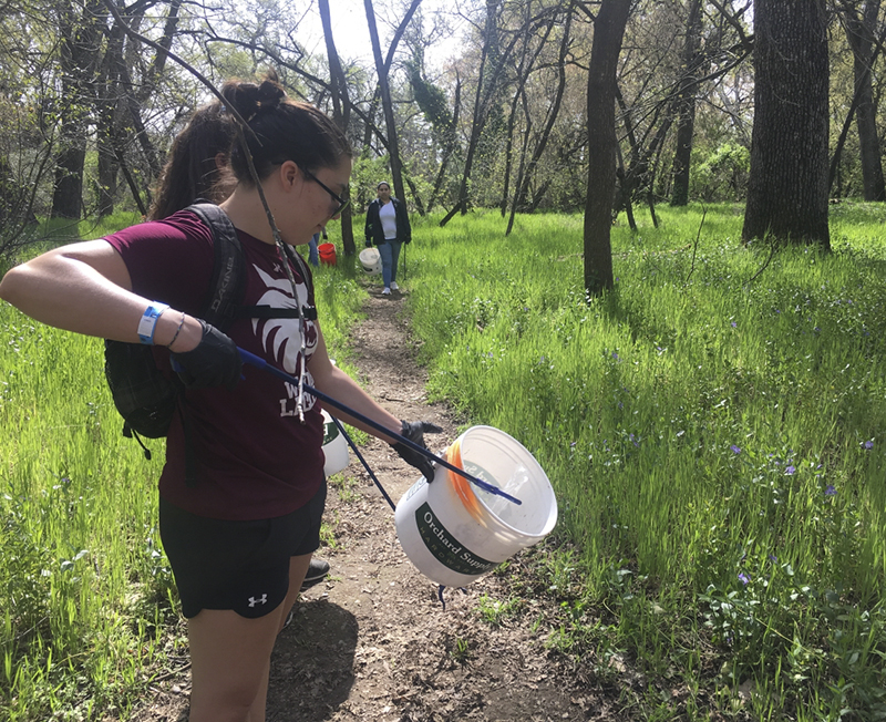 Janelle Bettencourt picks up trash in Lower Bidwell park with her lacrosse teammates. Photo credit: Lizzie Helmer