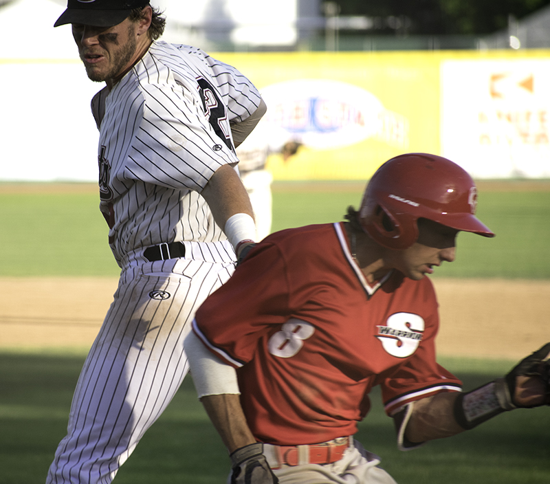 Chico State first basemanRJ Hassey tags out Stanislaus State's John Holleran at first base after a wild throw during the second game played on May 4. Photo credit: Martin Chang
