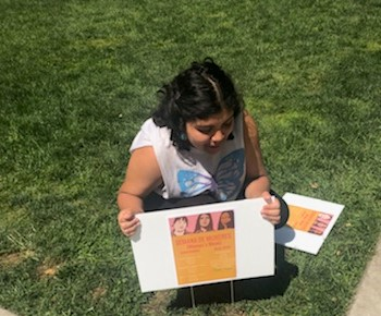 Diana Castellanos of M.E.Ch.A helps place signs around campus on Wednesday, announcing the weeks events. Image courtesy of Jessica Godinez. Photo credit: Josh Cozine