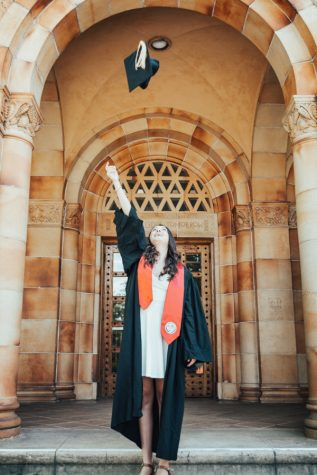 Graduation is around the corner and graduating senior Savannah McGhghy throws her cap in the air in front of Kendall Hall. Photo credit: Kate Angeles
