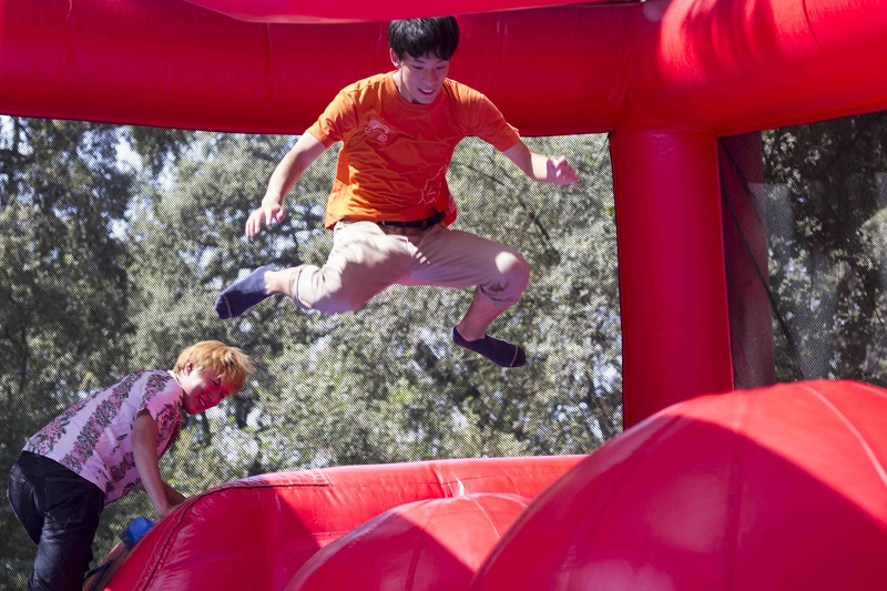 Tetta Ogawa jumps through the obstacle course while his friend Royeni Hasegawa watches him at Chico State's Bidwell Bash Sunday.