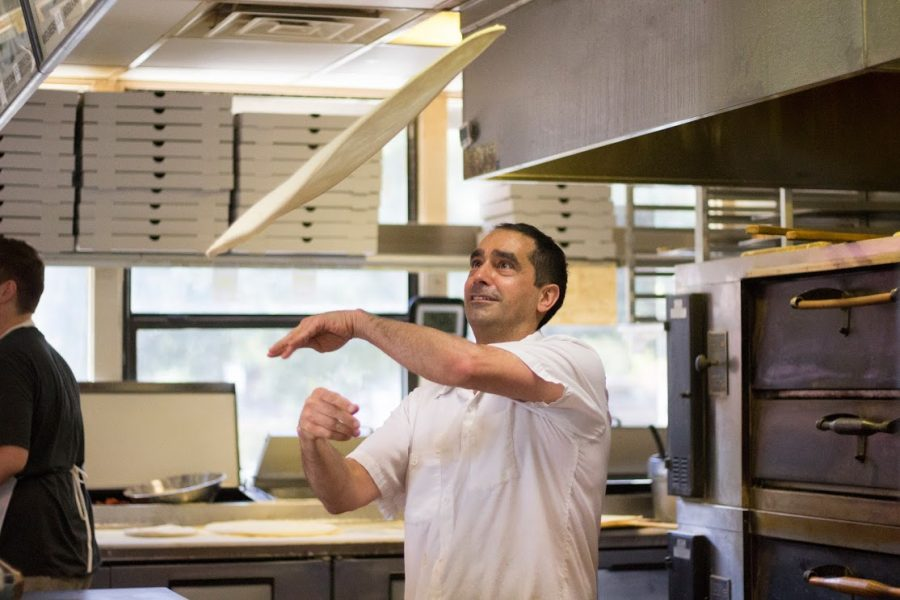 Enzo Perri tosses pizza dough to the desired form for Friday's dinner rush at Celestino's. Photo credit: Brian Luong