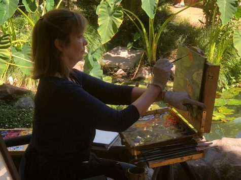 Janet Lombardi Blixt painting on a canvas during Chico Outdoor art festival Photo credit: Alex Coba