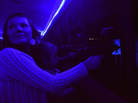 Stacy Lazzarino and her daughter are illuminated by the eerie blue light while shooting zombies at the Silver Dollar Fairgrounds Sunday night. Photo credit: Olyvia Simpson