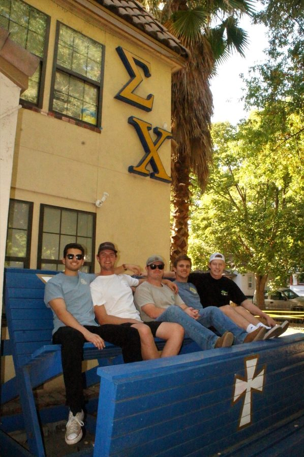 A group of Sigma Chi brothers sitting on the bench in front of the chapter house. Photo credit: Keelie Lewis