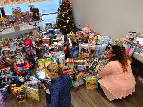 Kozette McGowan and Miranda Hanley, a volunteer, work on sorting the donated toys into categories based on age. Photo credit: Olyvia Simpson