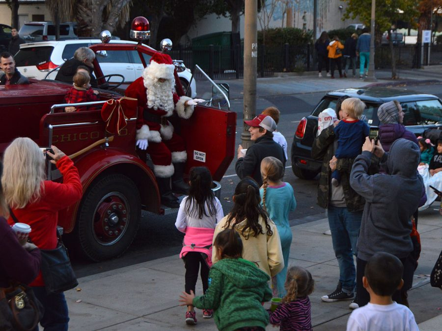 Children happily run up to greet Santa as he pulls up in a vintage firetruck to help light the Christmas tree in the downtown plaza. Photo credit: Olyvia Simpson