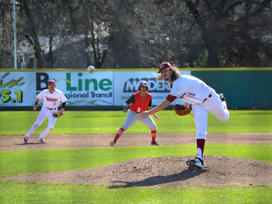 Grant Larson, a junior at Chico State, pitches an overhand serve against a Stanislaus State batter during a doubleheader game on Sunday. Feb. 17, 2019. Teammate and defensive shortstop, JT Navarro, watches the Stanislaus runner on second base.