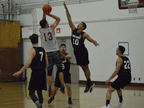 Andy Beronilla jumps up to block John Vega's shot on the basket at Monday night's practice on March 4, 2019. Photo credit: Olyvia Simpson