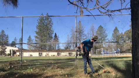 Charles Brooks mowing the grass in front of Paradise Adventist Academy for Make a Difference Day. Photo credit: Jessie Imhoff