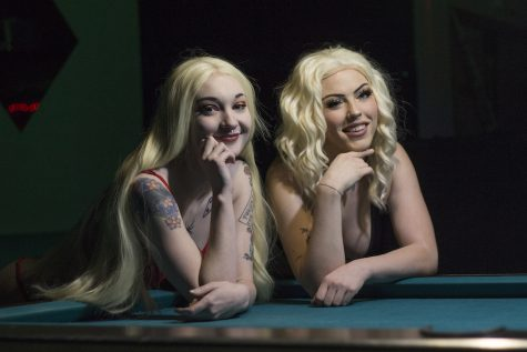 Sapphire (left) and Scarlett (right) are two of Centerfolds' dancers are smiling and posing in front of a pool table. Photo credit: Brian Luong