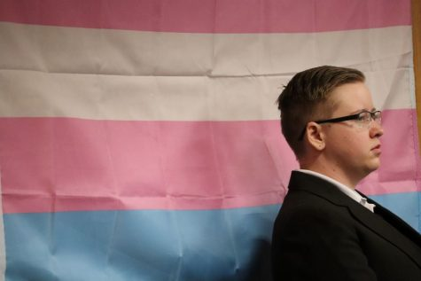 A volunteer stands alone along side the trans flag. Photo credit: Mary Vogel