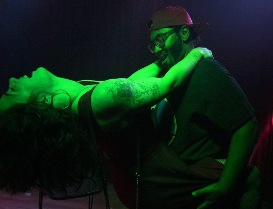 A performer dances on an audience member at a drag show