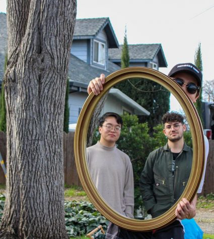Brian Luong and Matteo pose within a frame at the opening event for Second Bloom Supply.