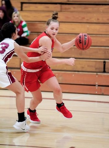 Stella Rollo moves up the court with the ball in a game for Denver East High School in Denver, Colo.