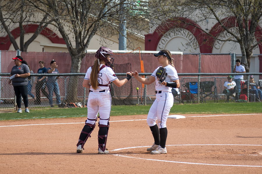#15 catcher Sara Mitrano (left) gives #14 pitcher Brooke Larsen (right) a fist pump in a softball game at Chico State (Ryan McCasland/Chico State Sports Information)
