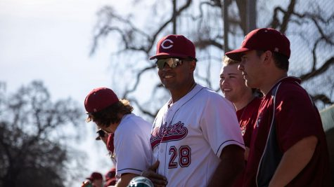 Chico State closer Kristian Scott stands on the sideline with teammates.
